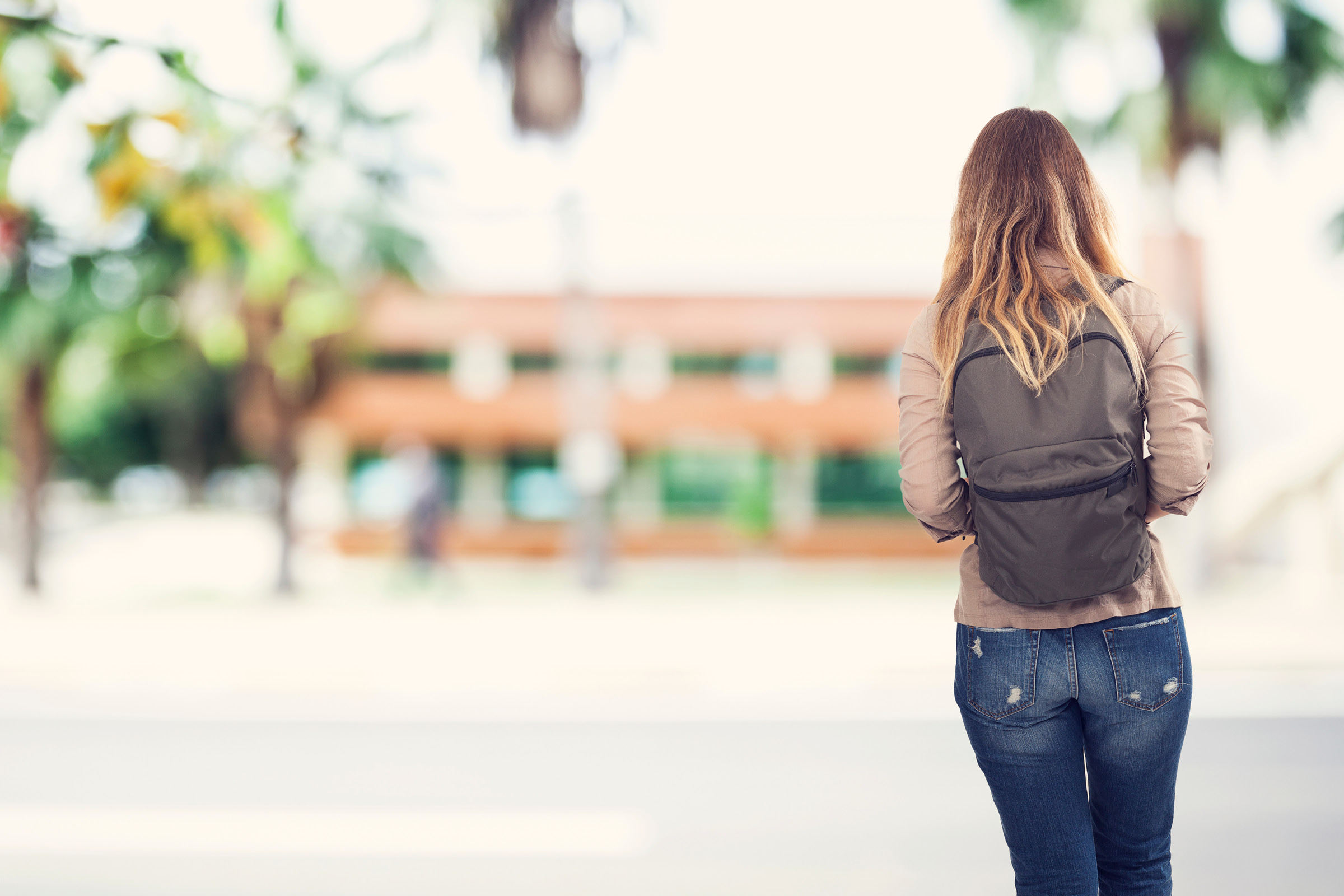A woman with a backpack on walking towards a university.