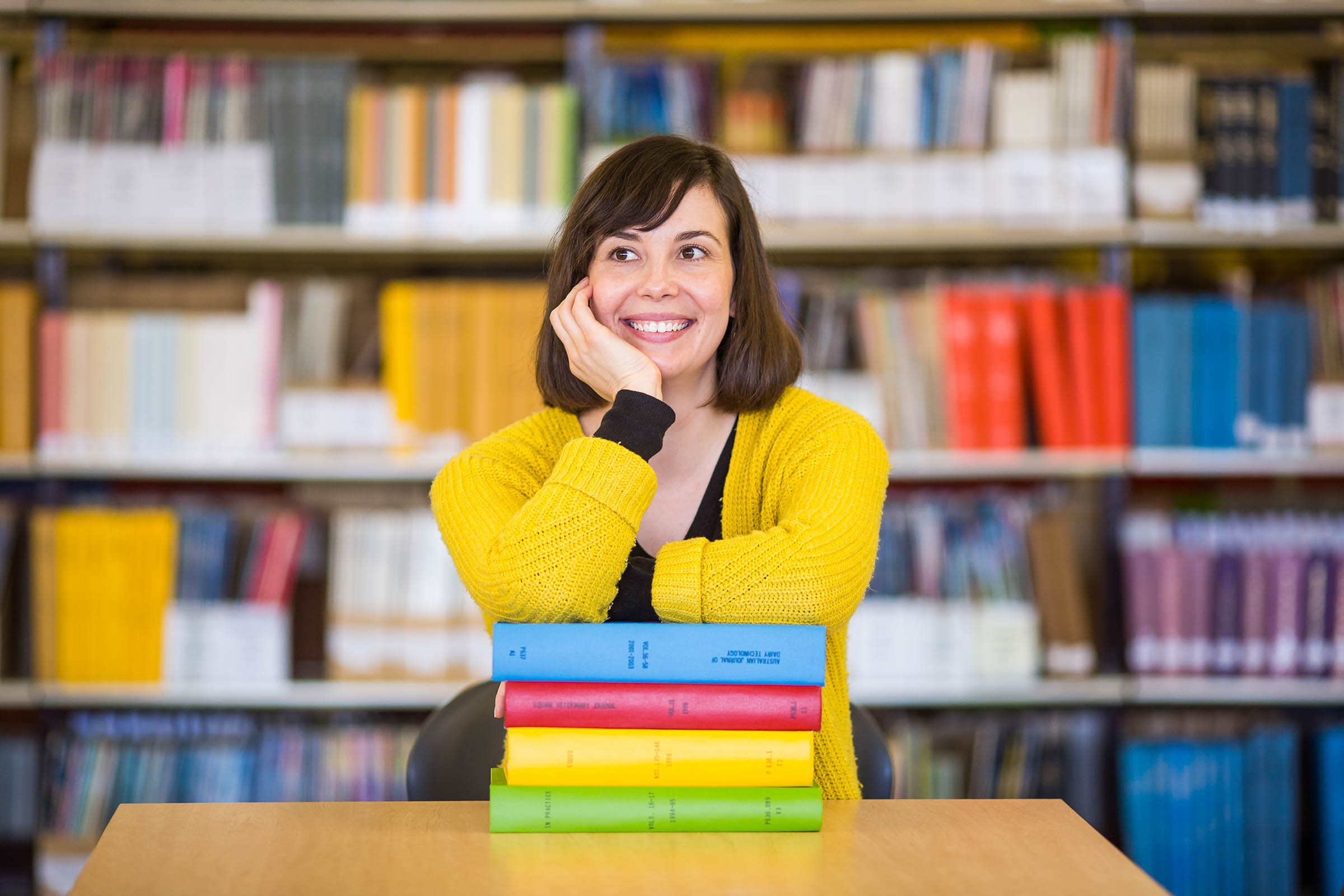 Woman leaning on a pile of books considering upskilling