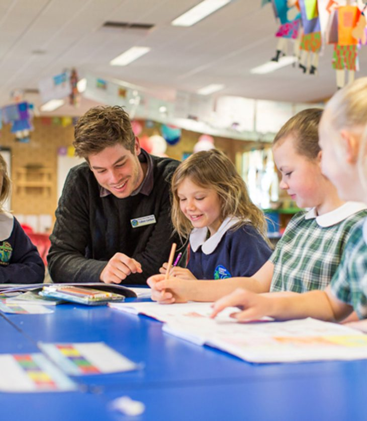 Male teacher talking to four primary students
