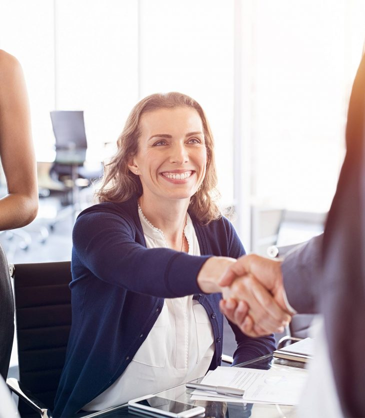 Woman shaking applicants hand at successfully getting a job
