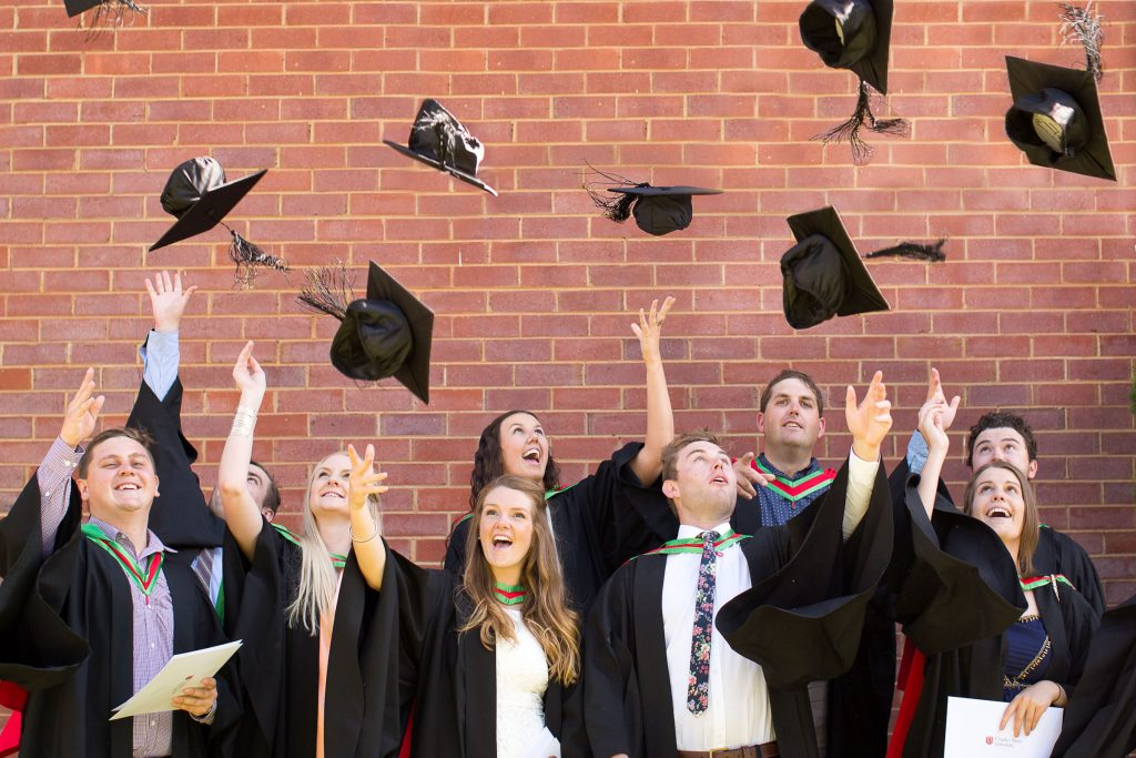 People celebrating graduation from postgraduate study by throwing their caps into the air