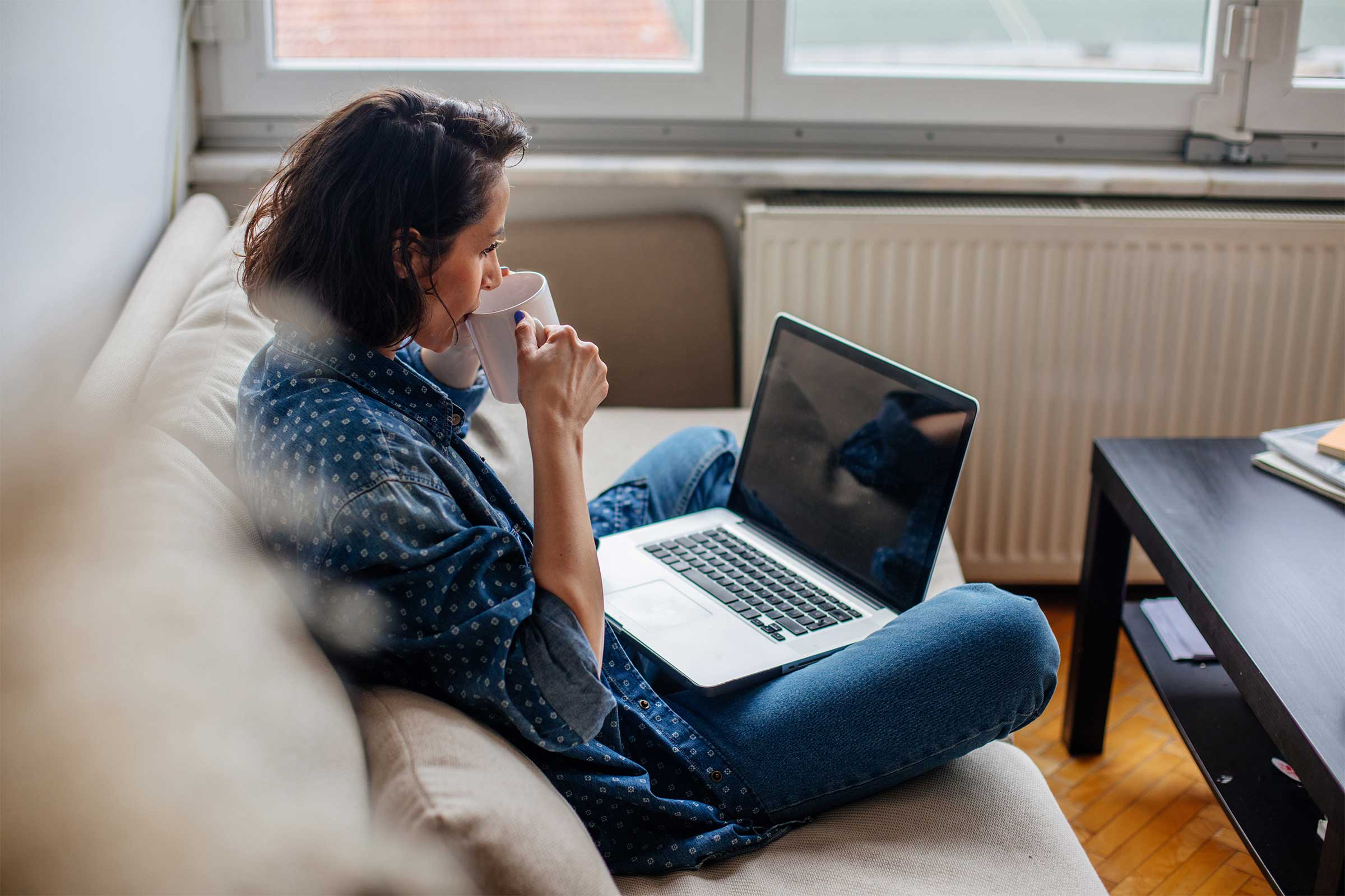 Woman sitting on couch studying and drinking tea