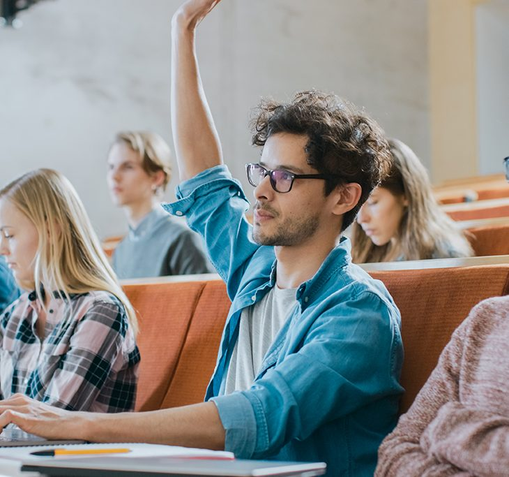 Student raising hand in lecture
