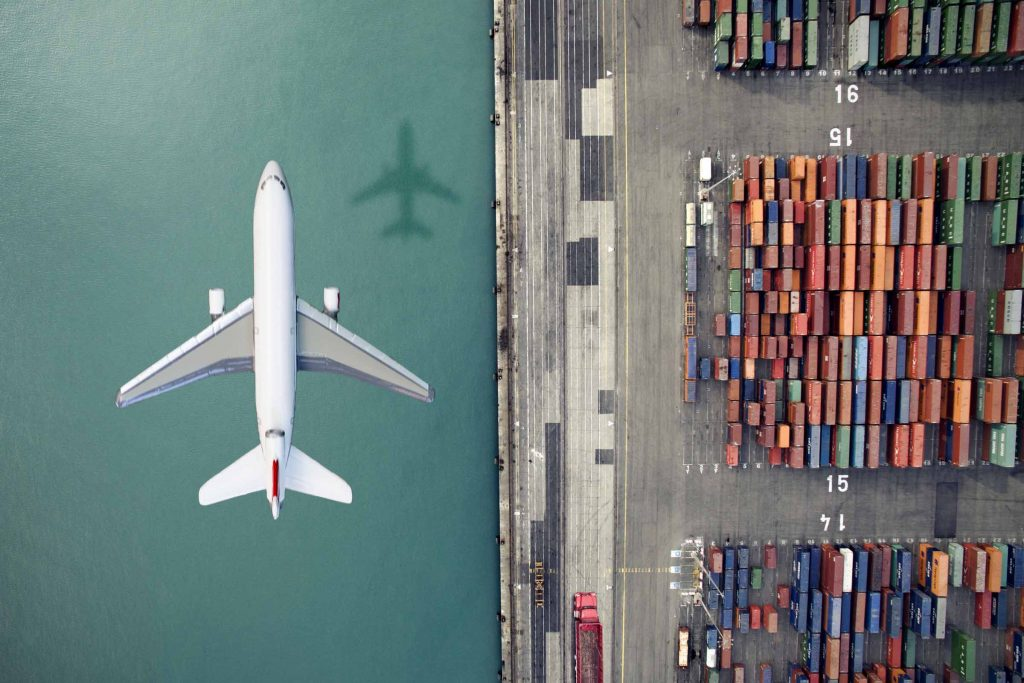 Plane flying next to a container dock