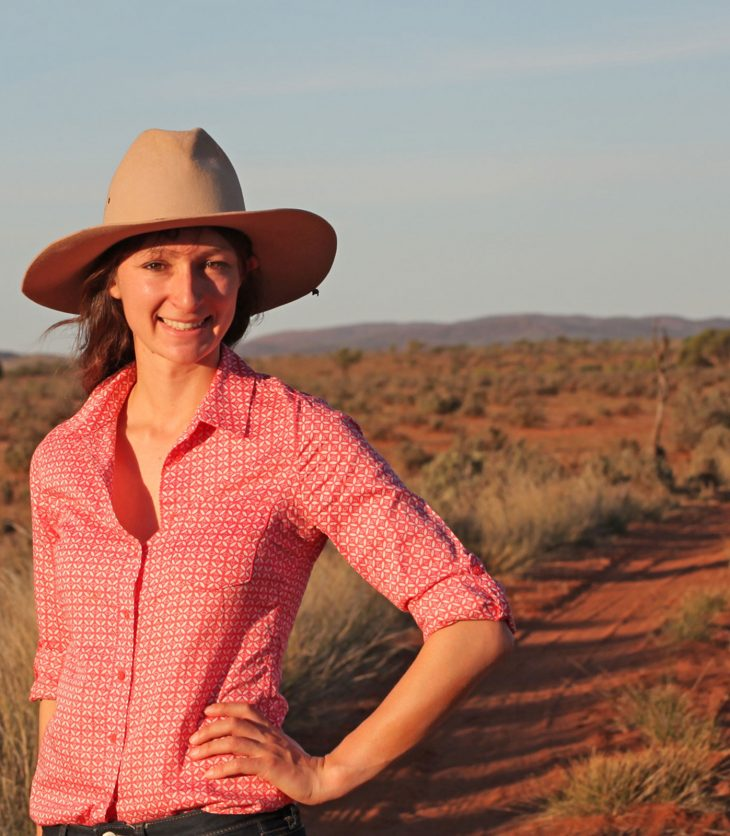 Anika Molesworth in hat on a red dirt road