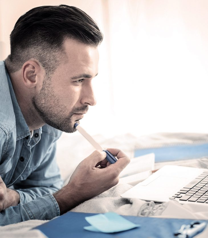 Man looking intently at a laptop screen
