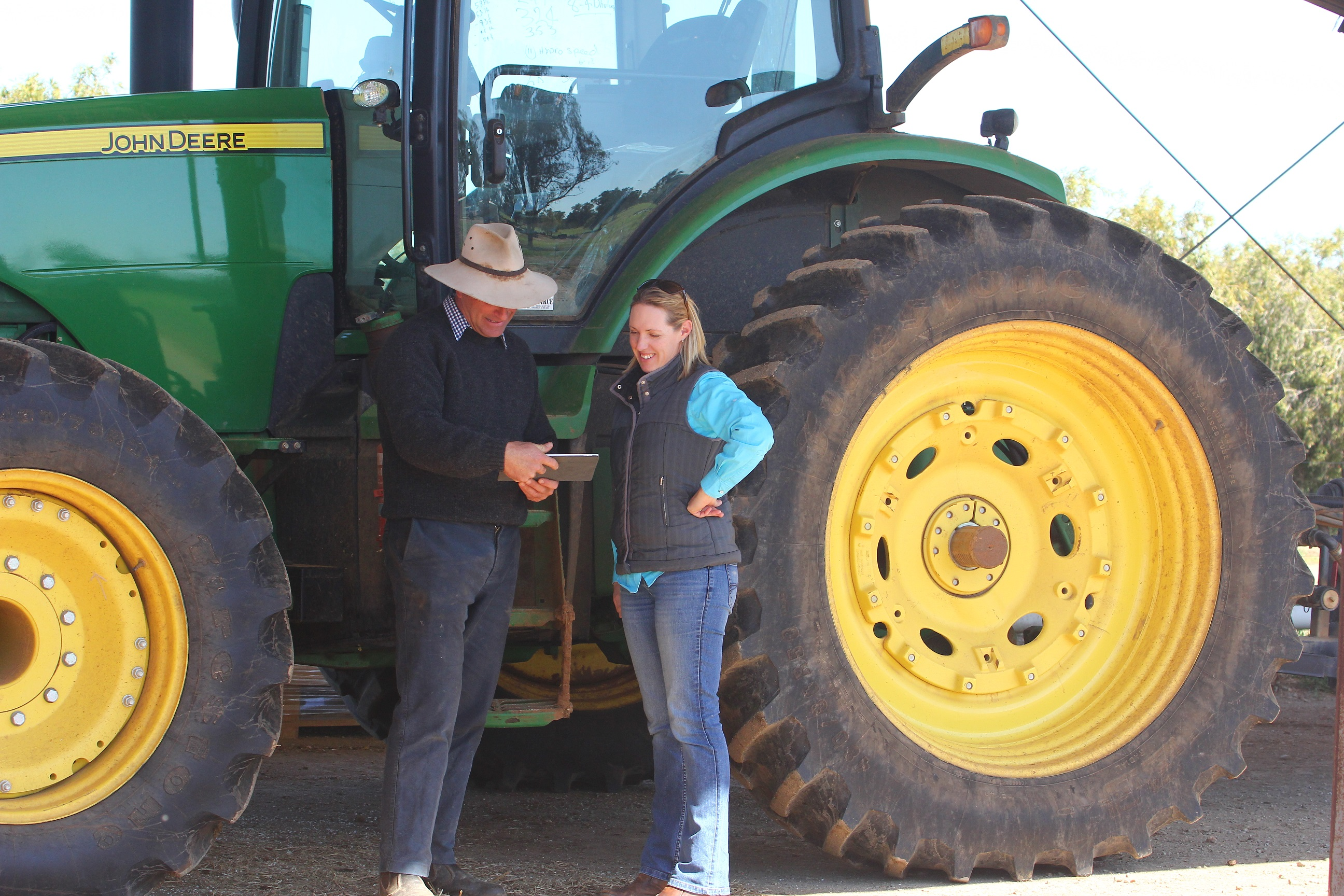 James Stephens, Charles Sturt's farm manager and Dr Alison Southwell looking at digital agriculture information on an iPad while standing in front of a large tractor.