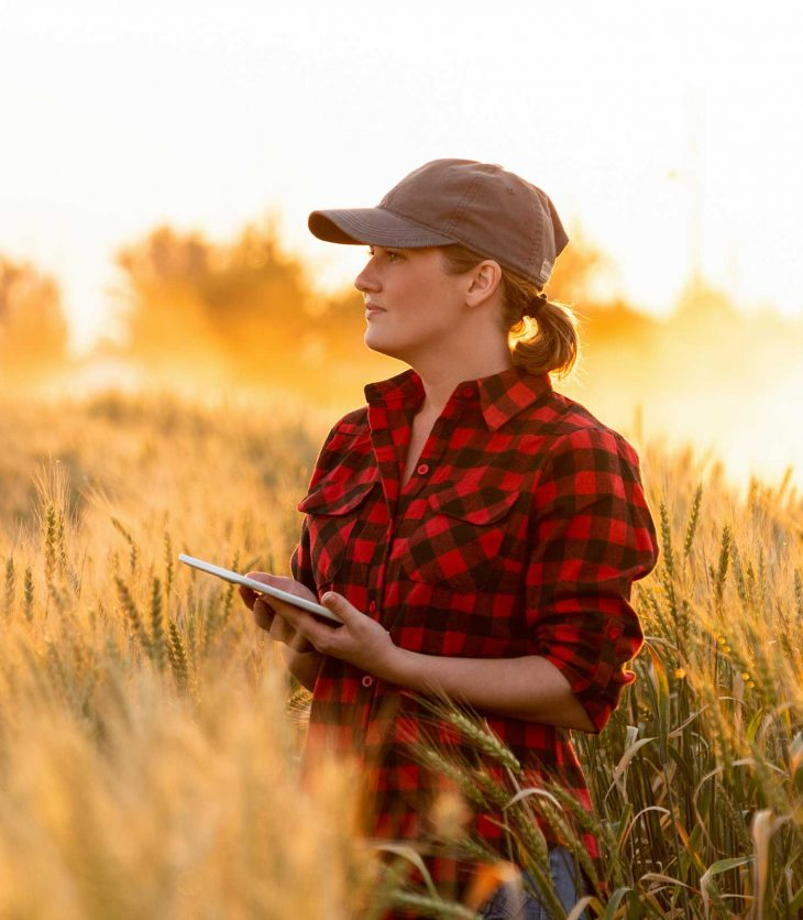 Woman standing in a field suing a tablet to perform geospatial science equations
