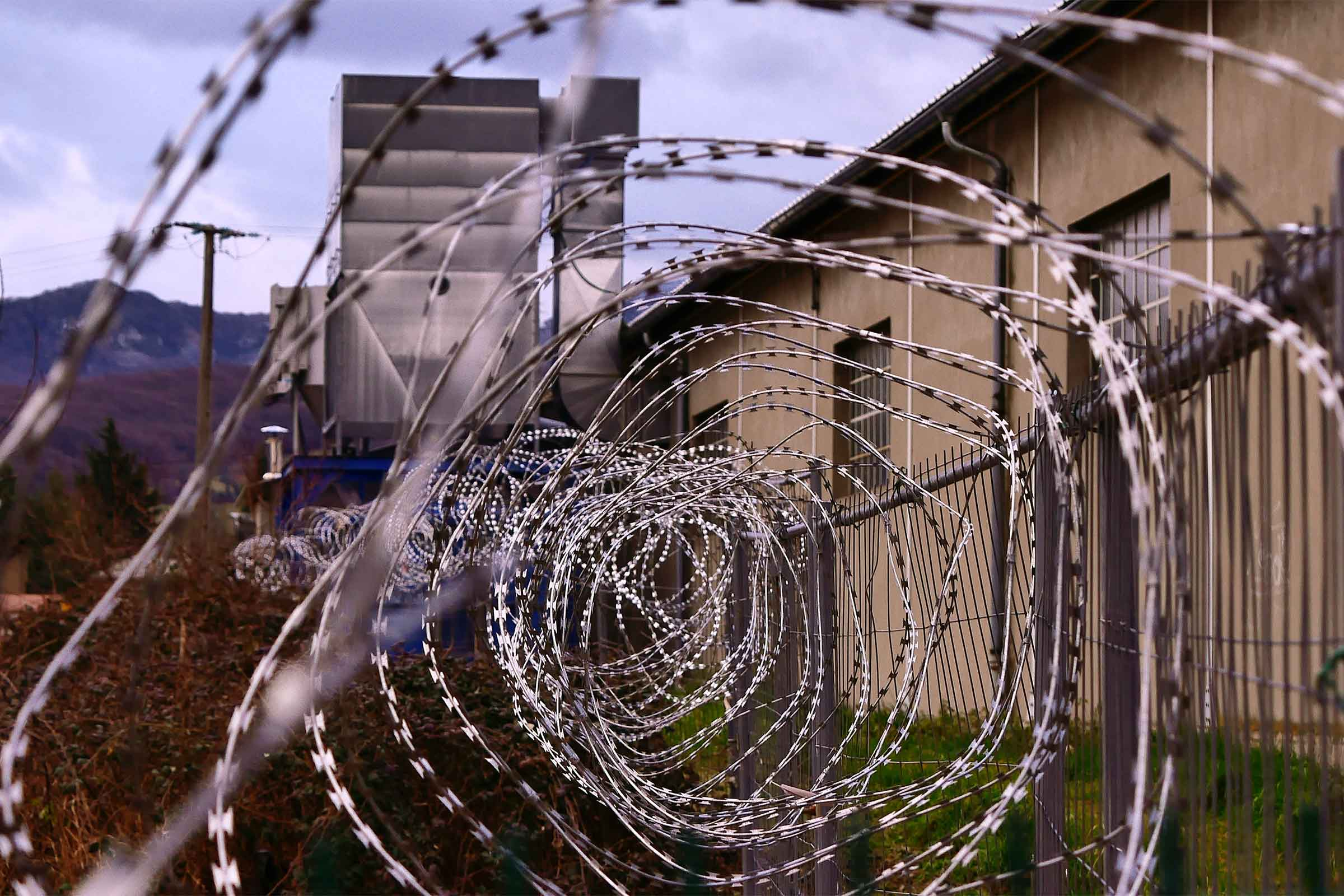 Razor wire in front of a prison building