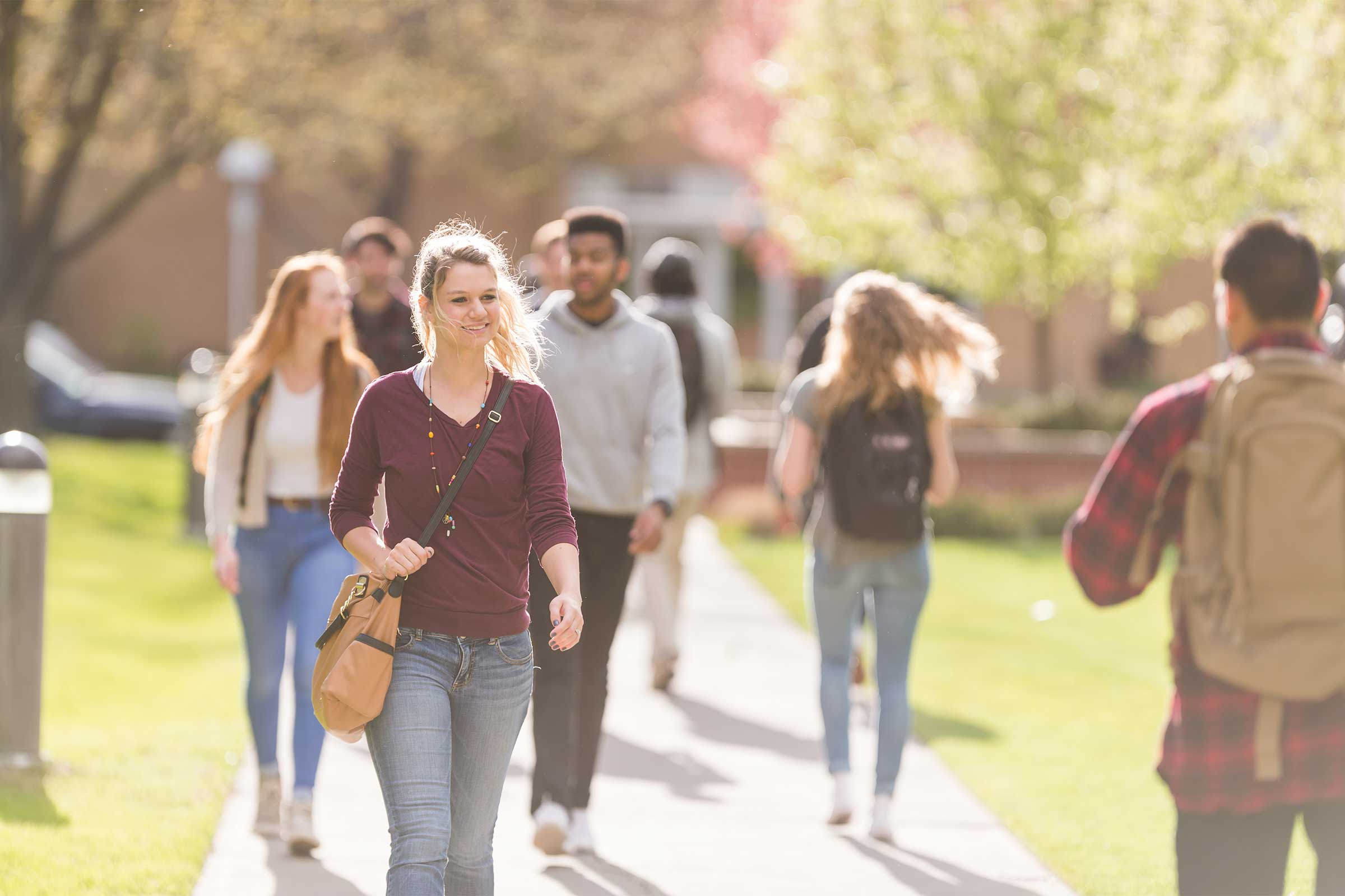 Female student walking across campus surrounded by fellow students