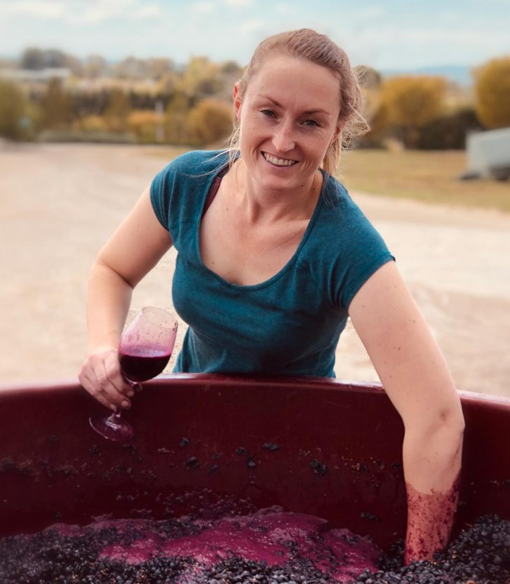 Woman stirring grapes and holding a glass of wine