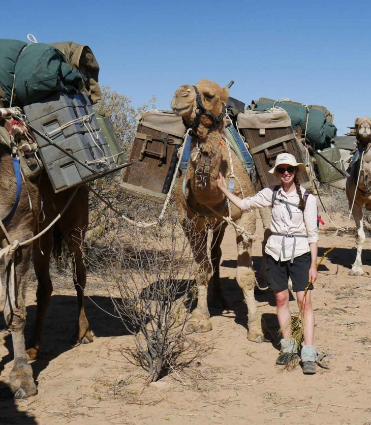 Charles Sturt student with camels in the desert on a fieldwork trip