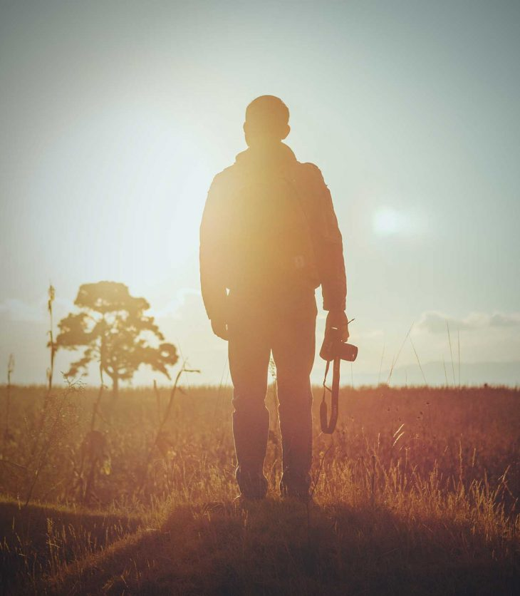 A man is standing in a field, back to the reader. He holds a camera by his side. It's important we develop an understanding of why the arts are important to our regions.