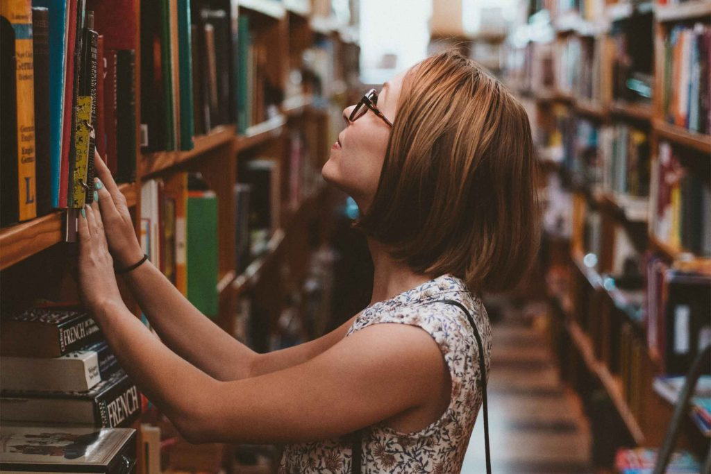Woman in library looking up at books. Explore information studies at Charles Sturt University and see where it can take you.