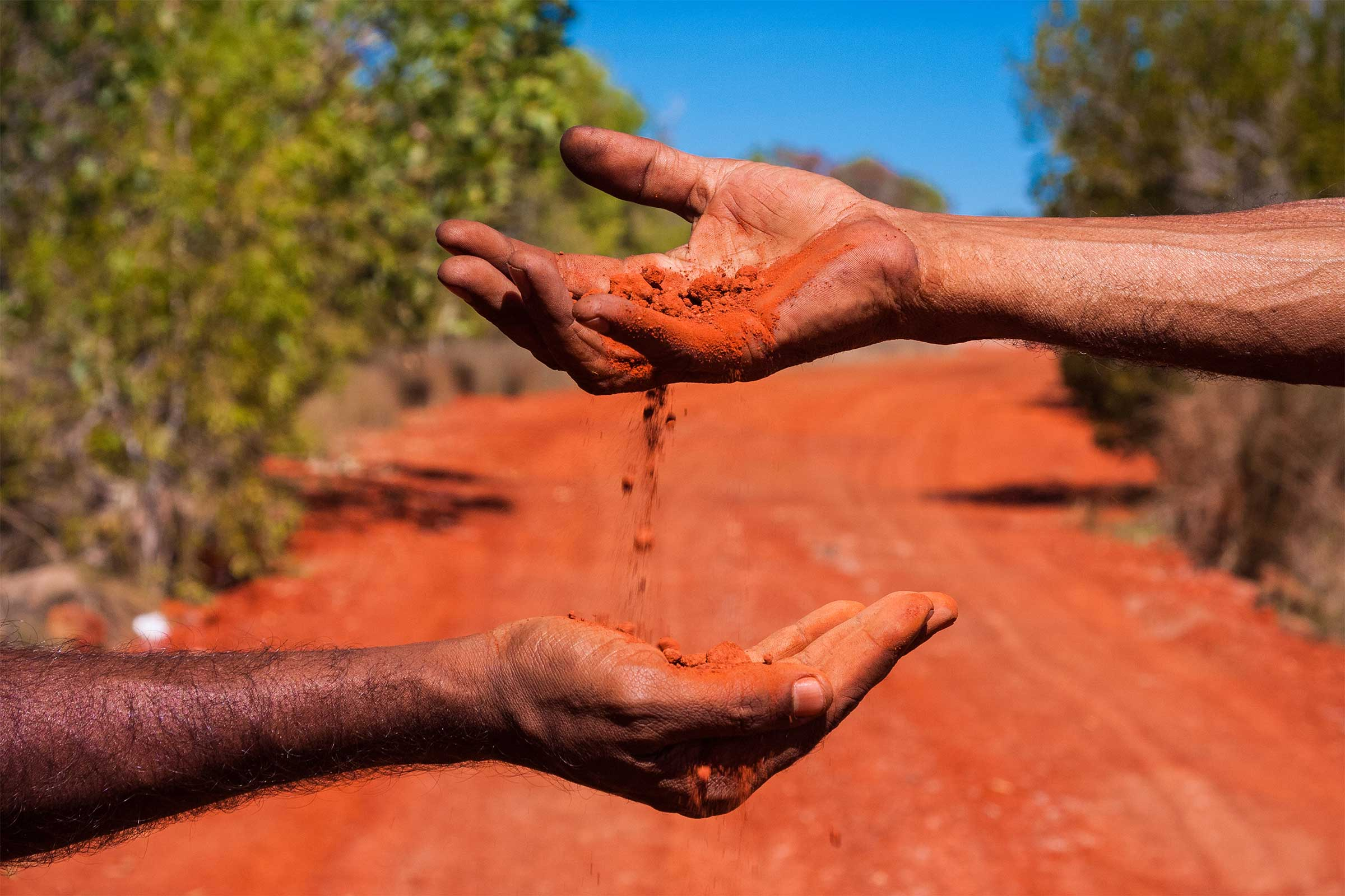 Two hands exchanging red dirt