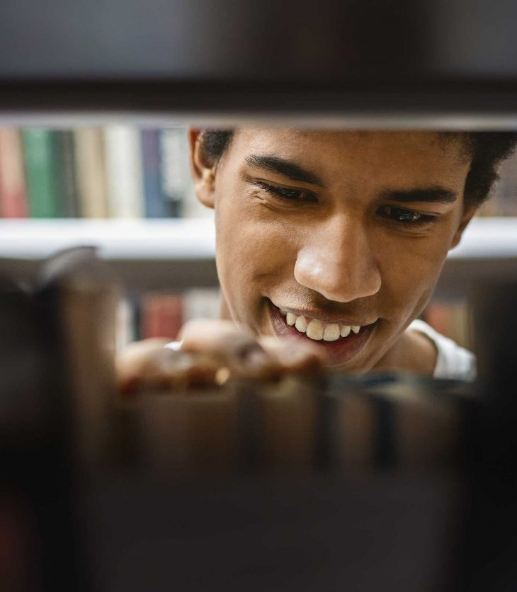 Smiling male student in library looking a text books.