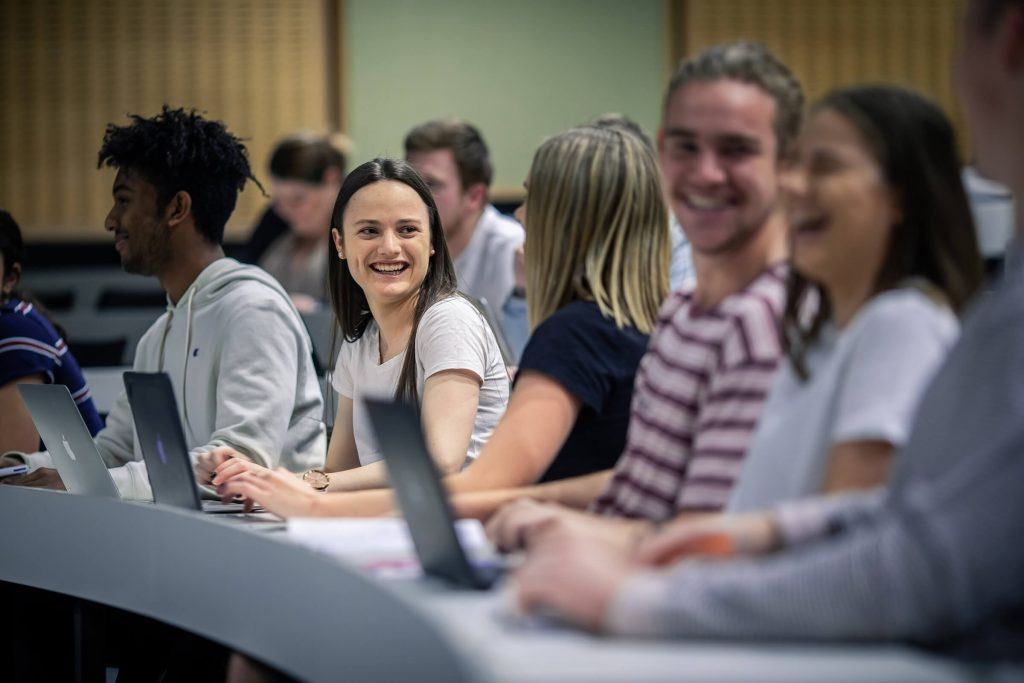 Smiling students working on laptops in a Charles Sturt University lecture room.