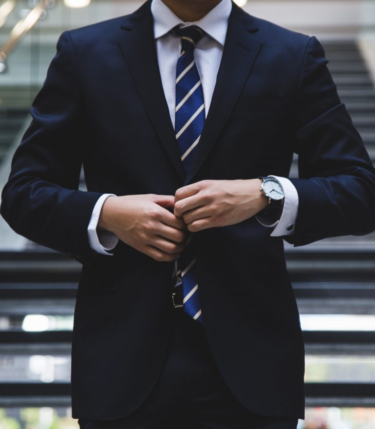 Professional man in a suit buttoning his jacket ready for to get promoted.