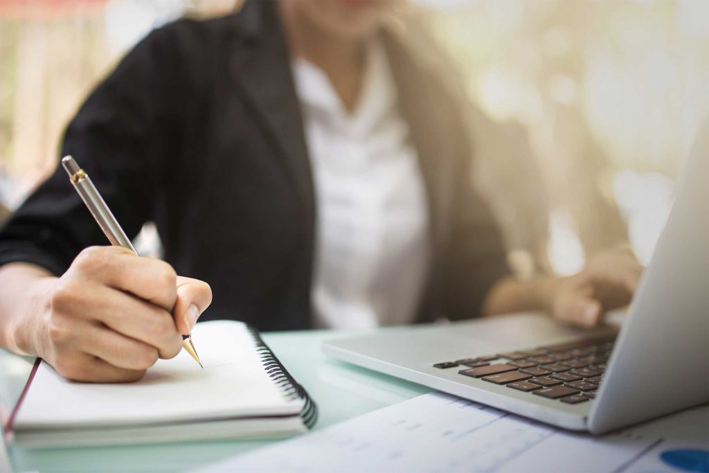 Close up of woman working on a laptop while writing on a notepad.