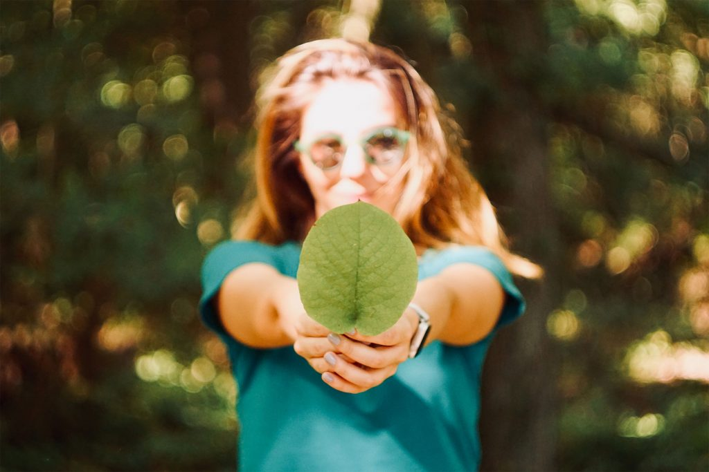 Happy young woman holding broad vibrant green leaf in outstretched arms.