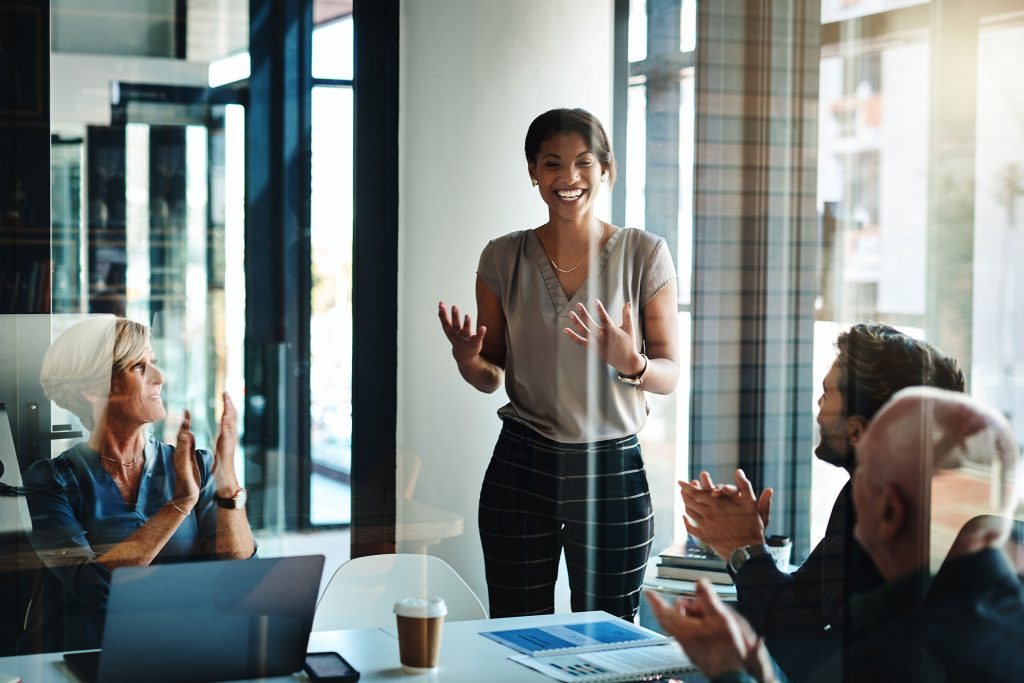Smiling woman full of self-confidence presenting in meeting while co-workers applaud