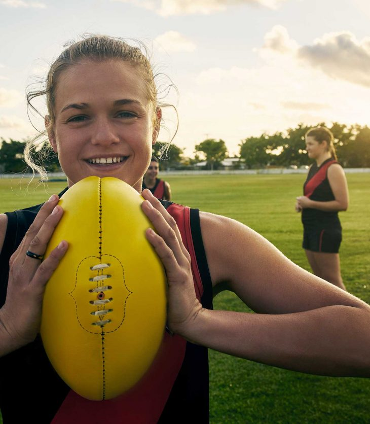 Female elite athlete holding a rugby ball