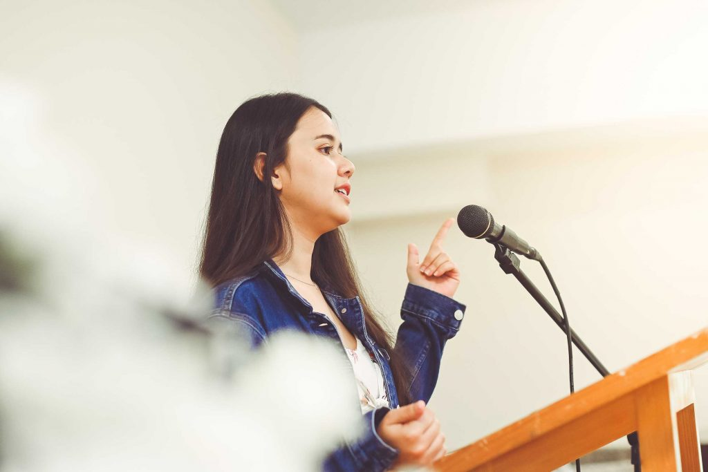 Female school student using her soft skills in public speaking