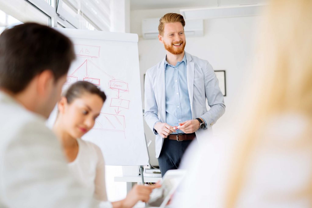 Smiling male employee engaged in skill development as he presents to colleagues in a meeting