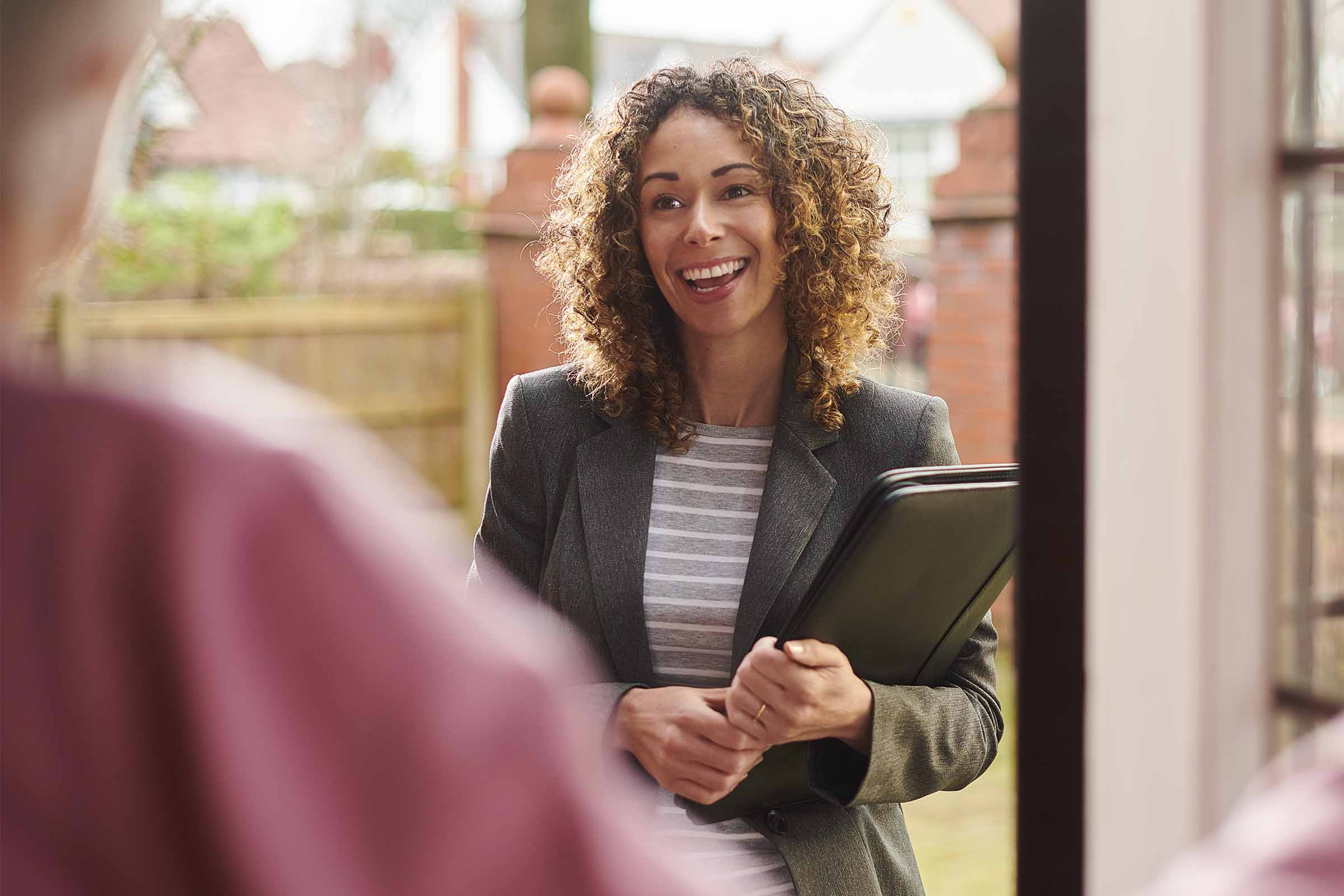 Smiling female social worker with clipboard at the doorstep to a house
