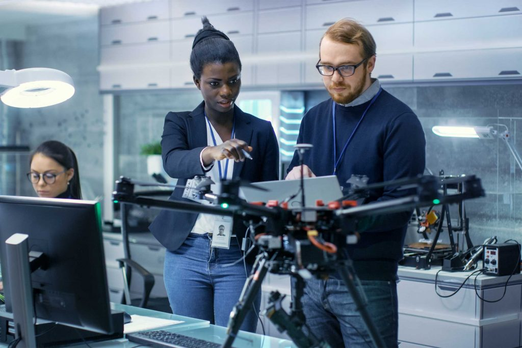 two people in front of a drone discussing notes