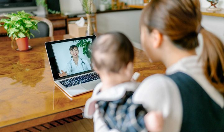 Woman with child speaking to a doctor via a telehealth conference on a laptop