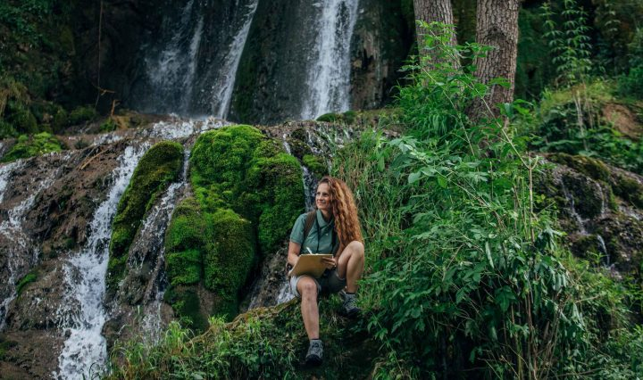 Young woman sitting by waterfall pondering jobs in environmental science