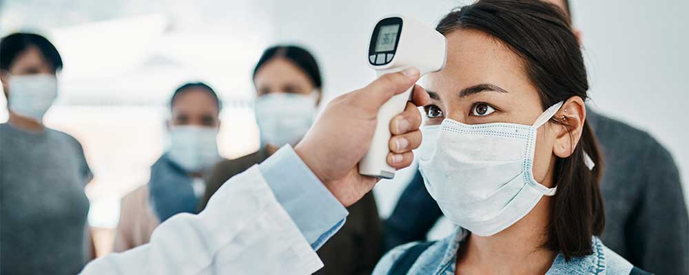 Group of people wearing face masks, one woman getting her temperature checked using a digital thermometer