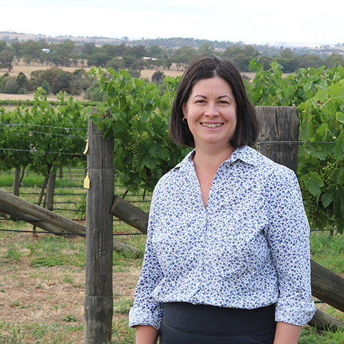 An image of Anne Johnson standing in front of a vineyard